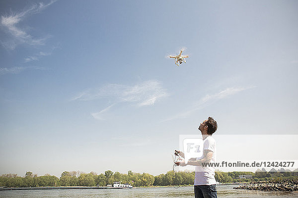 Man flying drone at a river