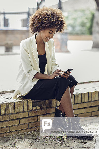 Smiling young woman with curly hair sitting on wall looking at cell phone