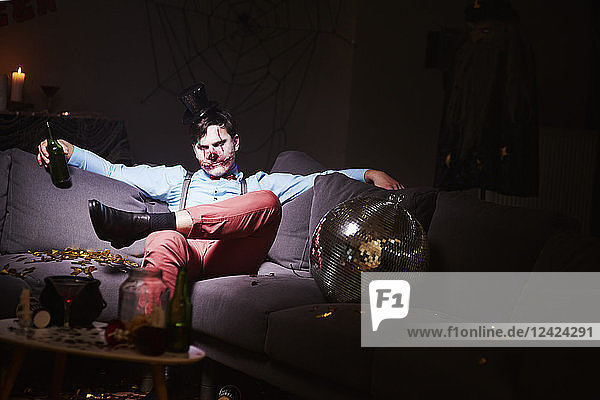 Man in Halloween costume sitting on couch after party  drinking beer Man in Halloween costume sitting on couch after party, drinking beer