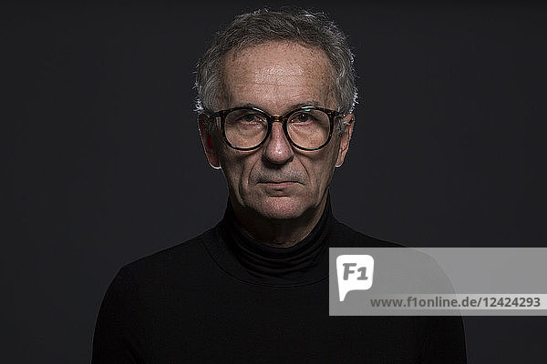 Portrait of serious senior man wearing glasses in front of dark background