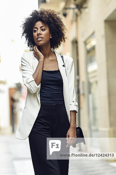Portrait of fashionable young woman with curly hair walking in the city