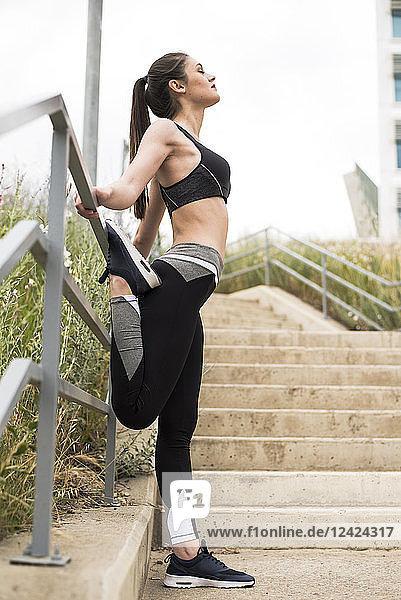 Sportive woman stretching leg