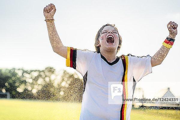 Boy wearing German soccer shirt screaming for joy  standing in water splashes