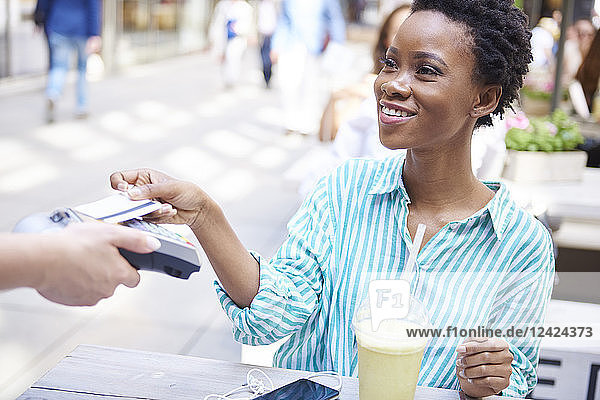 Portrait of smiling woman paying by credit card at pavement cafe Portrait of smiling woman paying by credit card at pavement cafe