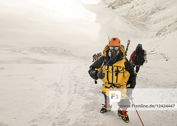 Nepal  Solo Khumbu  Everest  Sagamartha National Park  Roped team ascending  wearing oxigen masks