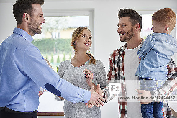 Family and real estate agent shaking hands in new apartment Family and real estate agent shaking hands in new apartment