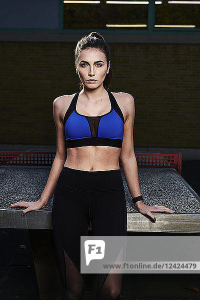 Sportive woman leaning on table tennis table