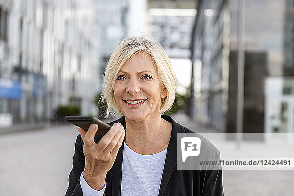 Portrait of smiling senior businesswoman using cell phone outdoors