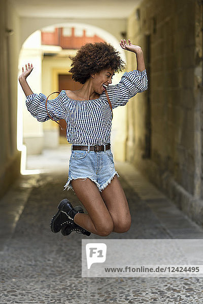 Laughing young woman jumping in the air