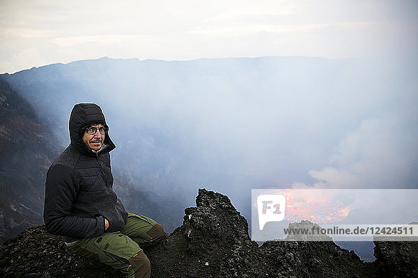 Africa  Democratic Republic of Congo  Virunga National Park  Man sittiing over Nyiragongo volcano crater