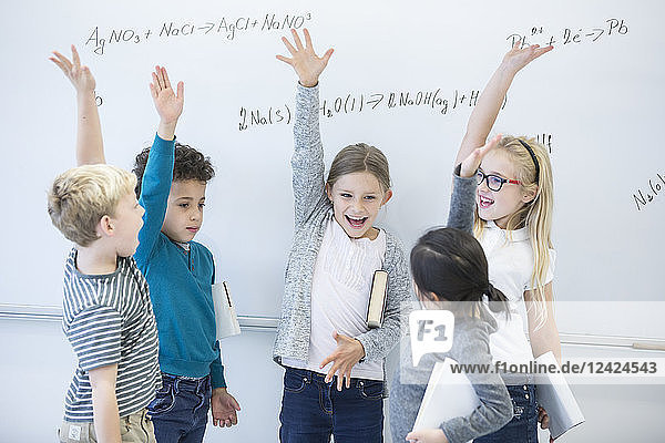Happy pupils raising their hands at whiteboard with formulas in class