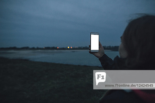 France  Brittany  Landeda  woman with cell phone at the coast at dusk