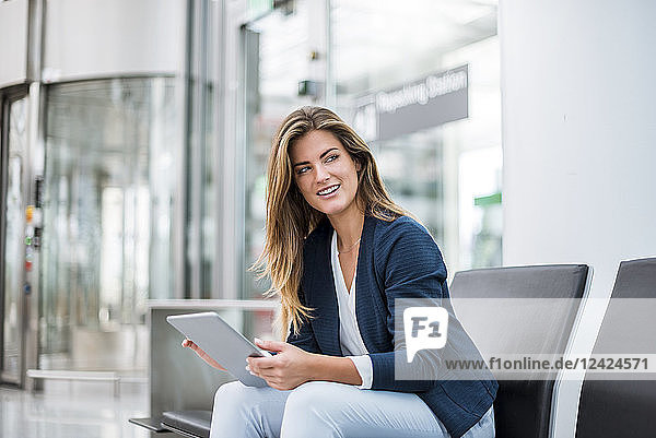 Young businesswoman sitting at waiting area using tablet