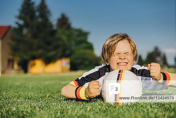 Boy in German soccer shirt lying on grass  keeping fingers crossed for world championship