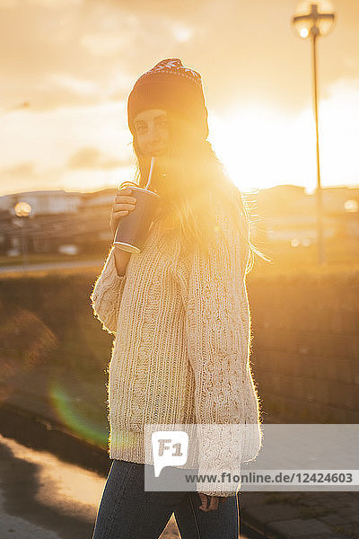Iceland  young woman with coffee to go at sunset