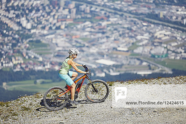 Austria  Tyrol  Woman mountain biking at Patscherkofel  Innsbruck in background