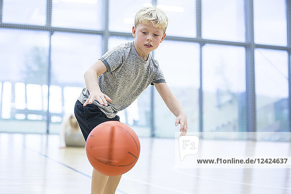 Schoolboy playing basketball in gym class