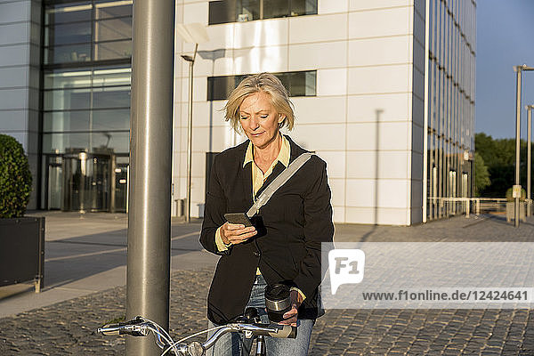 Senior woman with city bike and takeaway coffee using cell phone