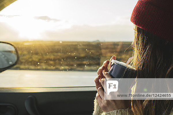 Iceland  young woman with coffee to go in car at sunset