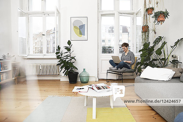 Woman sitting in chair at home  using laptop