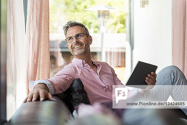 Smiling mature man sitting on couch at home holding a tablet