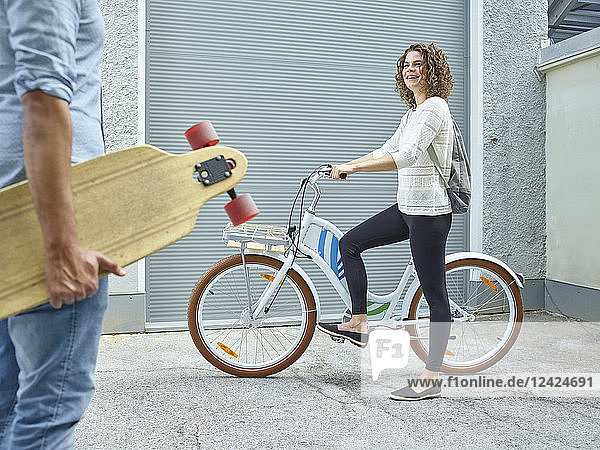 Man and woman with skateboard and bicycle