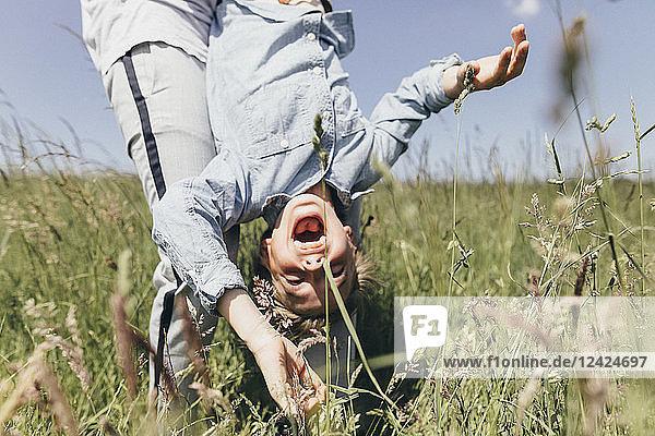 Man carrying happy boy in a field