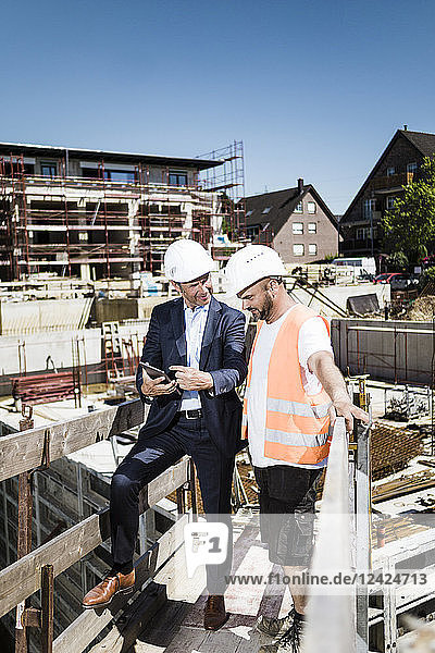 Man in suit with tablet talking to construction worker on construction site