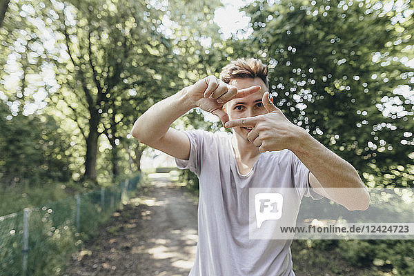 Young man making a finger frame on forest path
