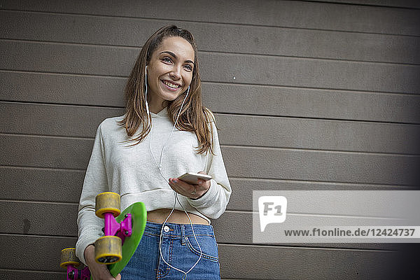 Smiling teenage girl with cell phone  earphones and skateboard