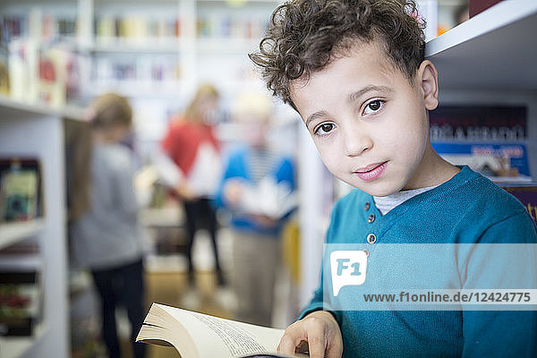 Portrait of smiling schoolboy with book in school library