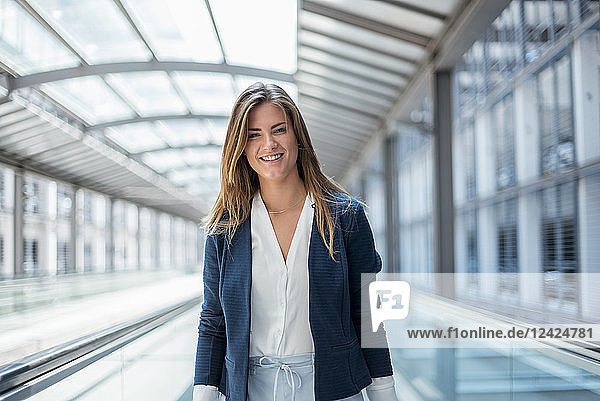 Portrait of smiling young businesswoman on moving walkway