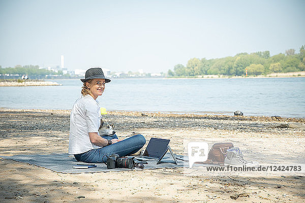 Smiling woman sitting on blanket at a river with dog and laptop