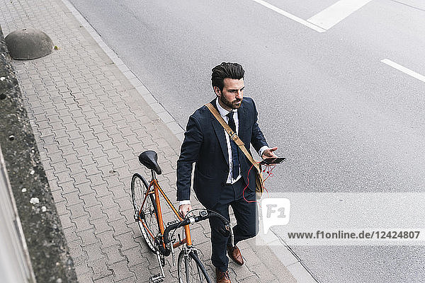 Businessman with bicycle and cell phone walking at the street