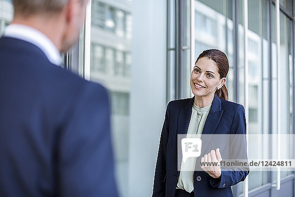 Portrait of smiling businesswoman face to face to business partner