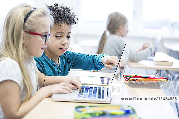 Schoolboy and schoolgirl using laptop together in class