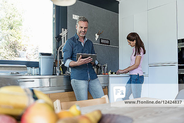 Couple in kitchen at home cooking and using a tablet