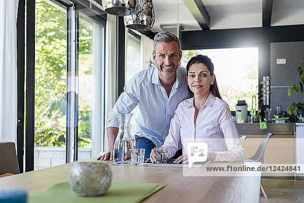 Portrait of smiling couple at table at home