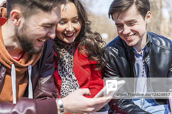 Russia  Moscow  group of friends at park  having fun together  using smartphones
