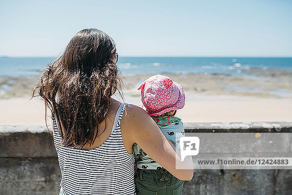 France  back view of mother and baby girl looking to the sea