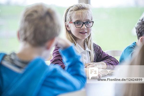 Portrait of smiling schoolgirl with classmates in class