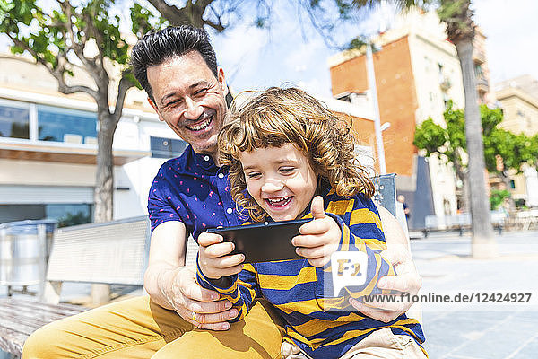 Spain  Barcelona  happy father and son with a smartphone sitting on bench