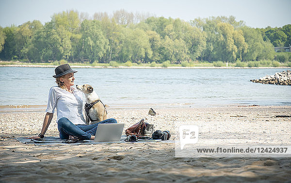 Woman sitting on blanket at a river with dog and laptop