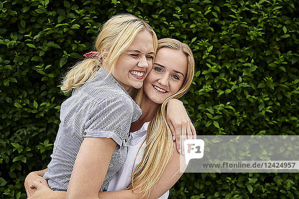 Two happy young women hugging a hedge