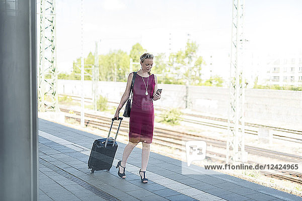 Mature businesswoman with smartphone and suitcase walking at platform