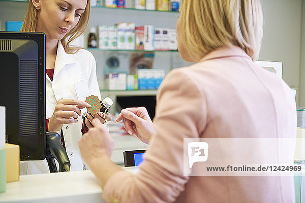 Pharmacist advising woman in pharmacy Pharmacist advising woman in pharmacy