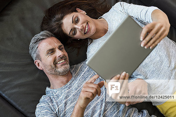 Happy couple lying on couch at home sharing a tablet
