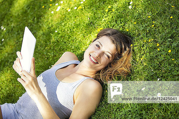 Young woman lying on meadow  using tablet