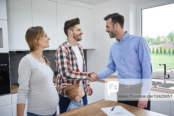 Family and real estate agent shaking hands in kitchen of new apartment Family and real estate agent shaking hands in kitchen of new apartment