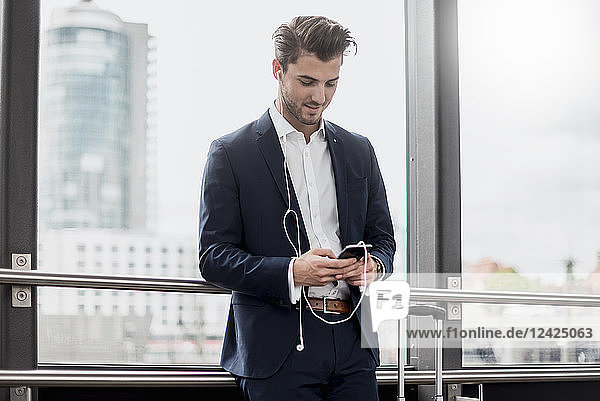 Young businessman at the window with cell phone  earbuds and rolling suitcase